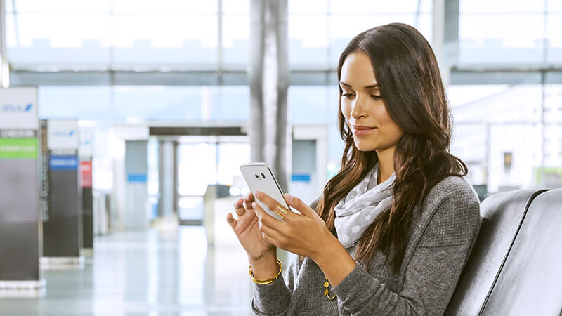 Woman at airport using smart phone