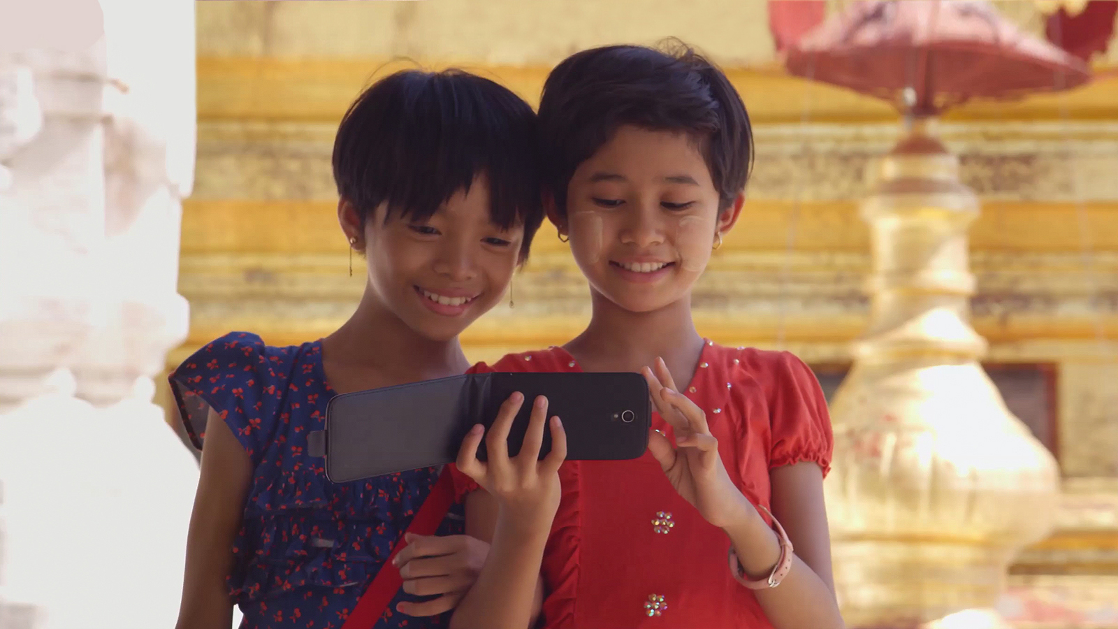 Two young girls looking at a phone together.