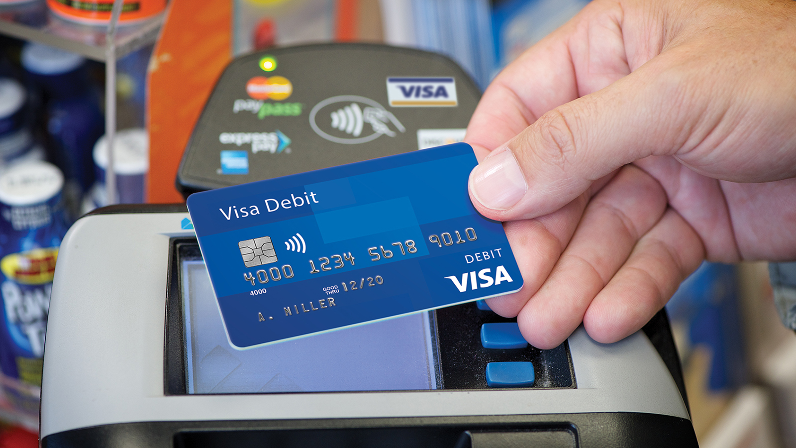 Presenting a contactless Visa debit card at checkout.